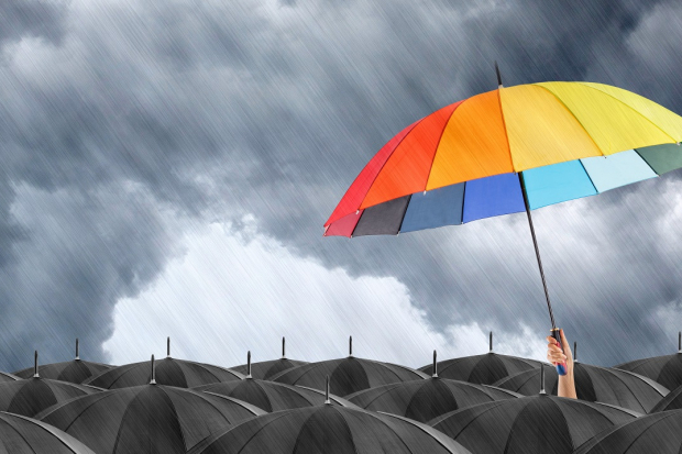 Rainbow umbrella stand out in a sea of black umbrellas